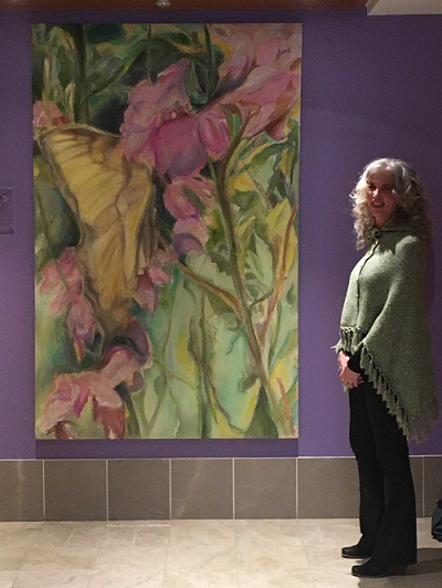 Elizabeth Bryan-Jacobs standing in front of donated painting